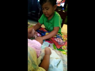The brother try to help put socks his sister *
