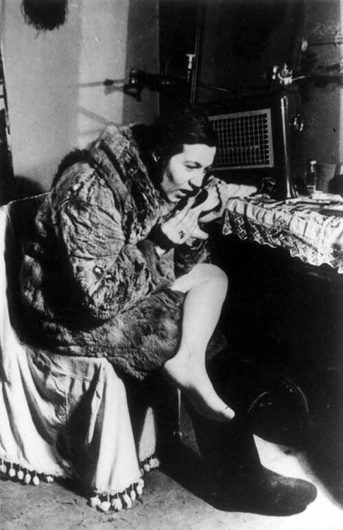 Актриса театра Музыкальной комедии Зинаида Габриэлянц согревает дыханием туфлю. Блокадная зима.